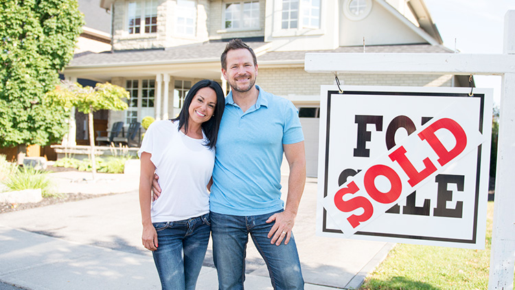 selling your house camden ny smiling couple in front of home with sold sign from christmas country homes